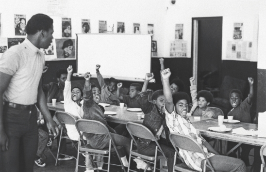 A teacher leads his students with the black power salute and slogans at a Black Panther liberation school.
